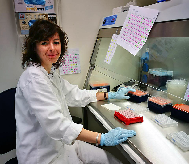 Woman in lab coat sitting in laboratory. Photo.